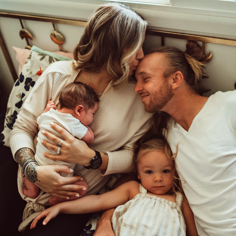 Postpartum Photography - a woman holds onto her new baby as she reached to kiss her husband next to her, their other daughter snuggles close distracted