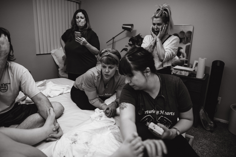 Birth Photography - A Family, grandmother and aunts to be,  all look on as woman gives birth to child