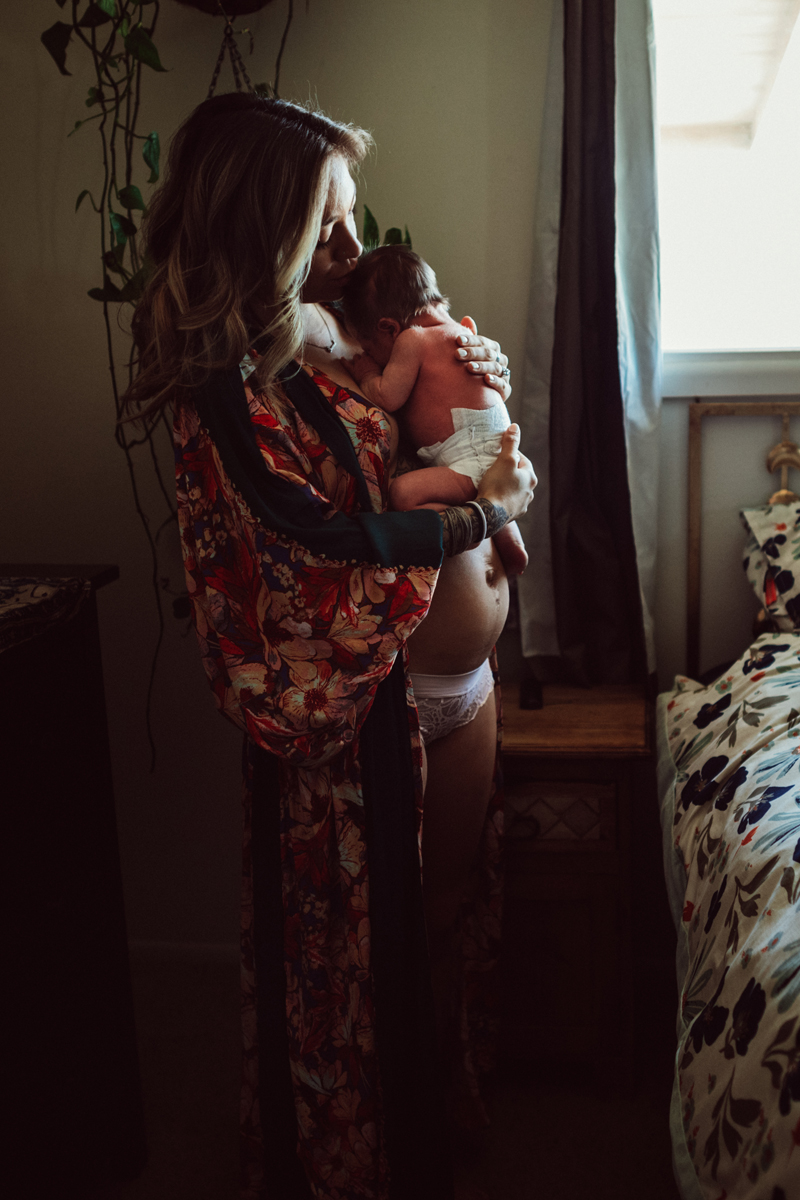 Postpartum Photography - A woman stands near her bed holding and kissing her newborn baby