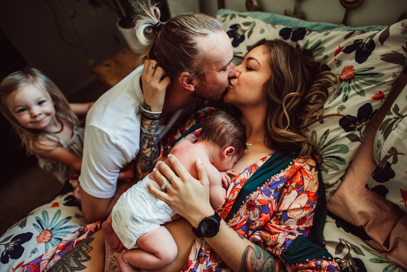 Postpartum Photography - a woman laying in bed with baby kisses her husband, their young daughter smiles from behind