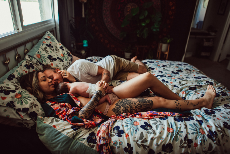 Postpartum Photography -  a man and woman snuggle in bed as they hold their baby close