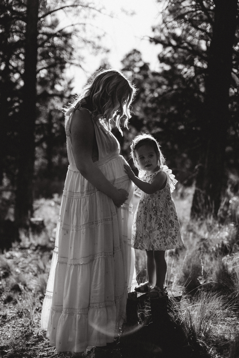 Maternity Photography - little girl places her hand on mom's pregnant belly.