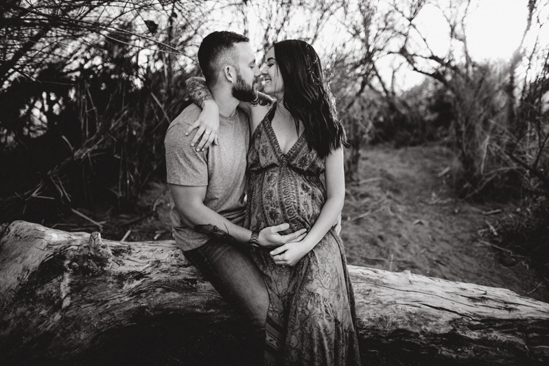 Maternity Photography - man and woman sit outside embracing nose to nose