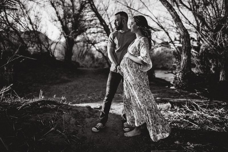 Maternity Photography - Man and pregnant woman stand outdoors, He has his hand on her belly