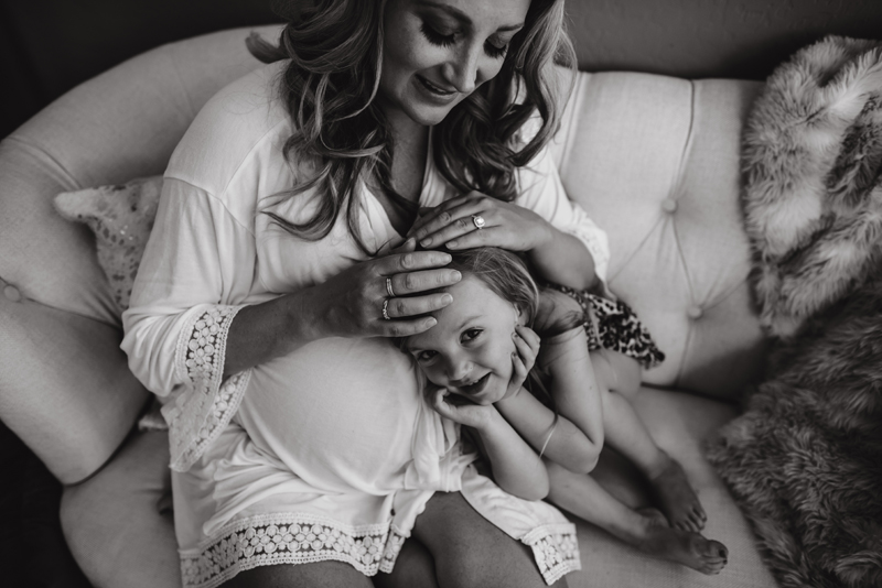 Maternity Photography - A Mother's little girl leans on her pregnant belly smiling in anticipation