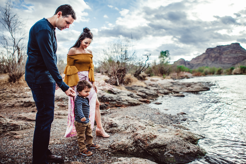 Family Photography -  Man, woman, and child walk near a flowing river outdoors