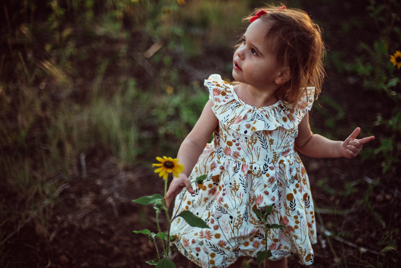 Family Photography - a little girl stands outside near a single yellow daisy