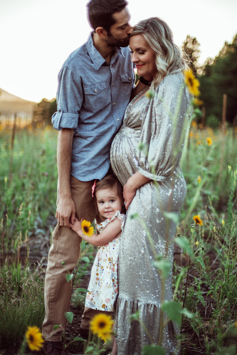 Maternity Photography - a family of 3 stand in a field of daises, dad, young daughter, and an expecting mother
