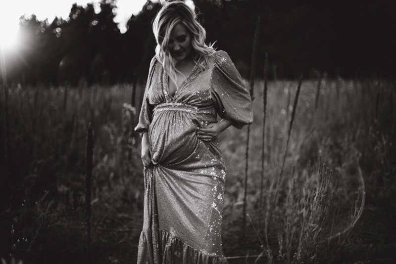 Maternity Photography - pregnant woman in an elegant dress stands in a field at golden hour