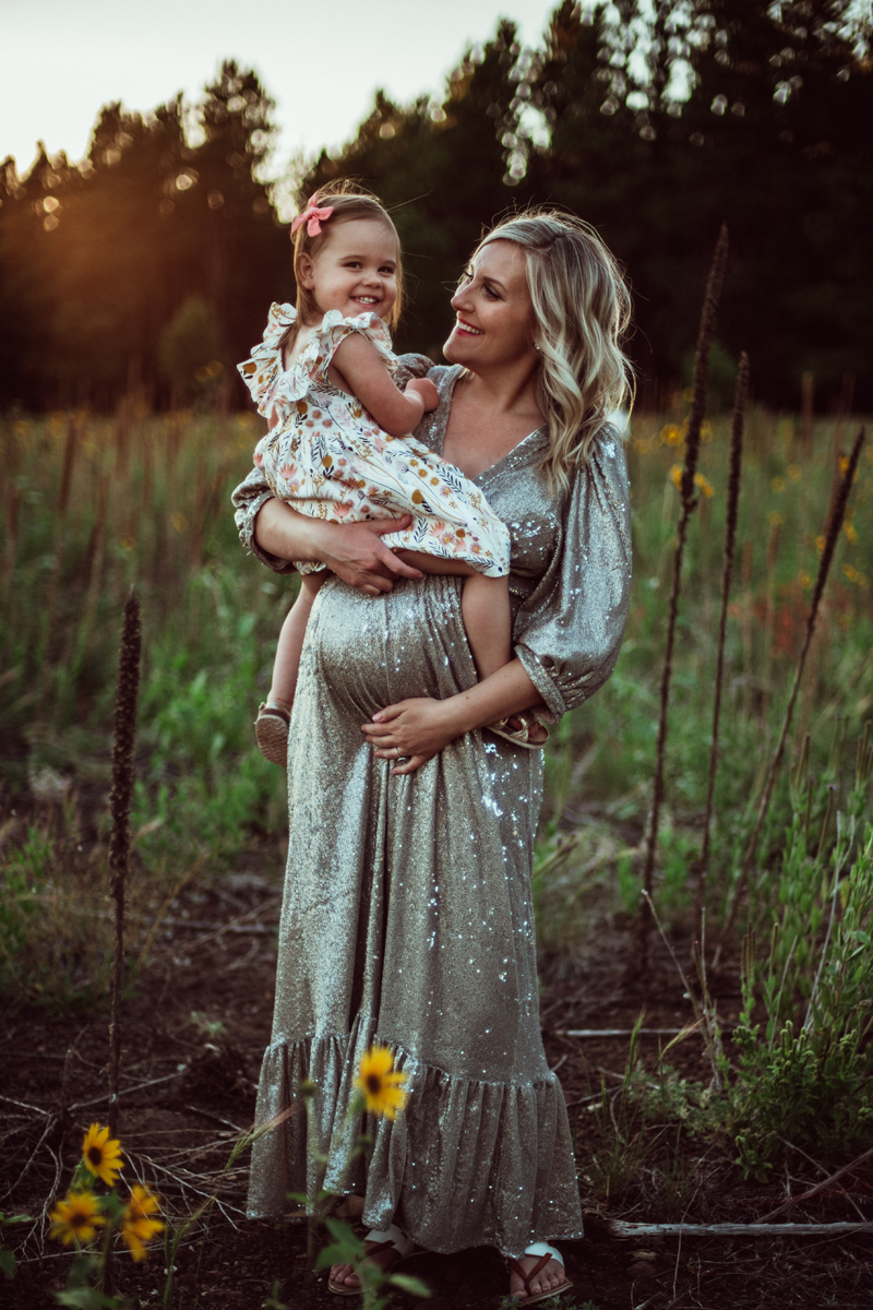 Maternity Photography - pregnant woman holds young daughter, she wears an elegant dress, both mom and daughter