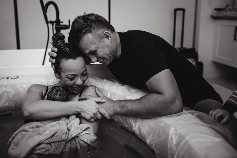Birth Photography - a dad leans in to celebrate mom as she holds their new baby
