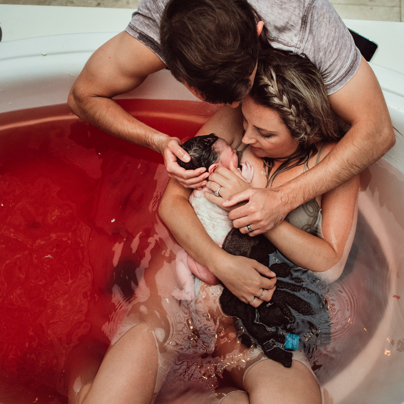 Birth Photography - a woman holds her newborn baby while in birthing tub, her partner holds her from behind
