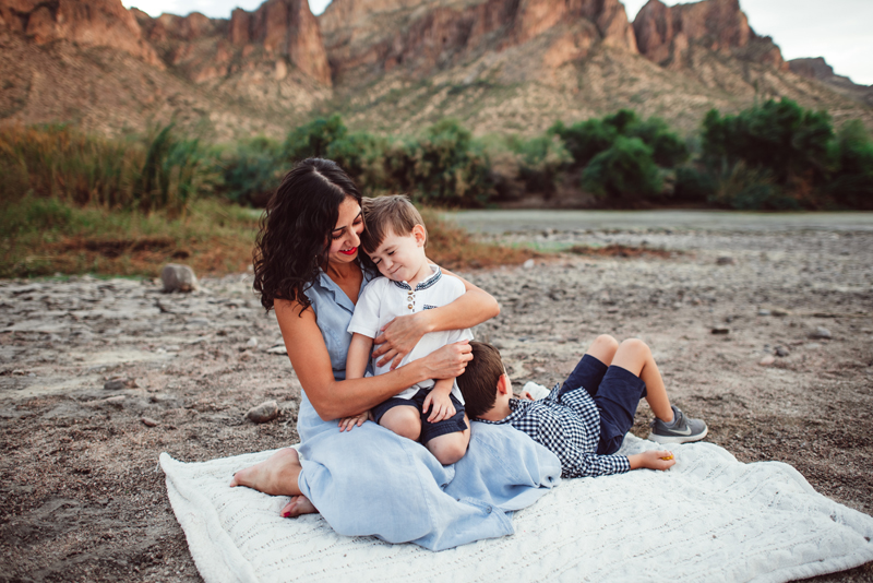 Family Photography - A mother holds onto her young son on a picnic blanket at the river, her other son leans on her.