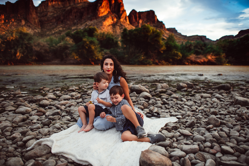 Family Photography - a woman and her two young boys sit on a blanket near the river's bank