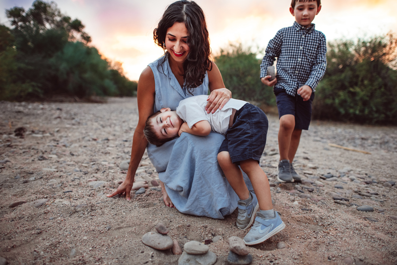 Family Photography - little boy smiles as he leans into his mom's lap, she laughs and other brother admires them nearby
