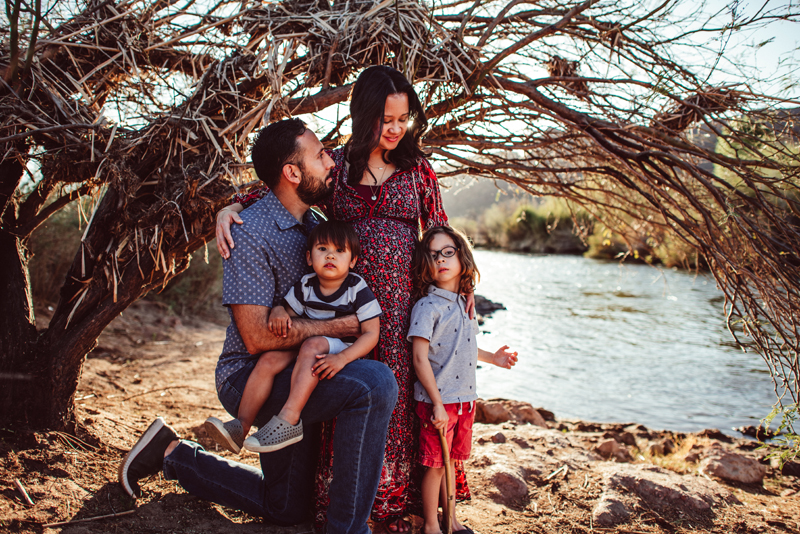 Family Photography - a family of four stand outdoors near the river