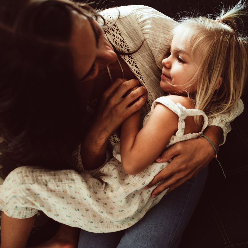 Family Photography - a mother holds her young happy daughter tightly