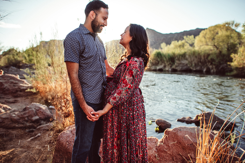Maternity Photography - Man and woman hold hands and look at each other, she is pregnant, they stand near river