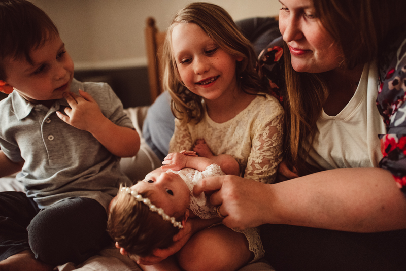 Family Photography - An older sister holds onto her newborn sibling, brother and mom look on
