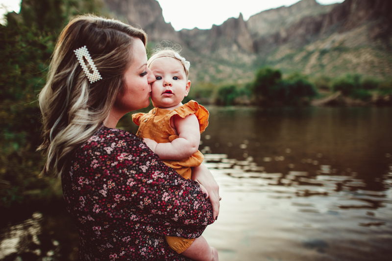 Family Photography - a mother holds her baby daughter as they stand near a river outdoors