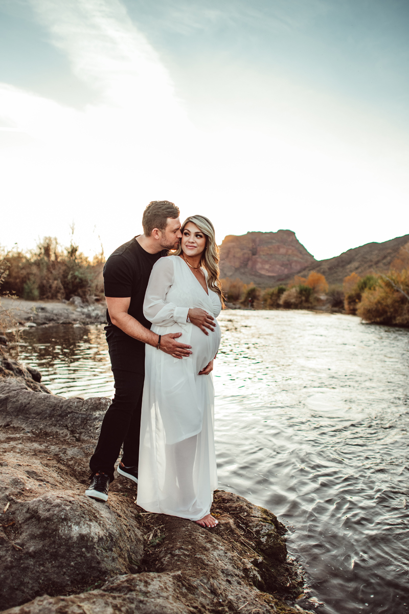 Maternity Photography - man kisses his wife and on cheek, they stand at the rivers edge