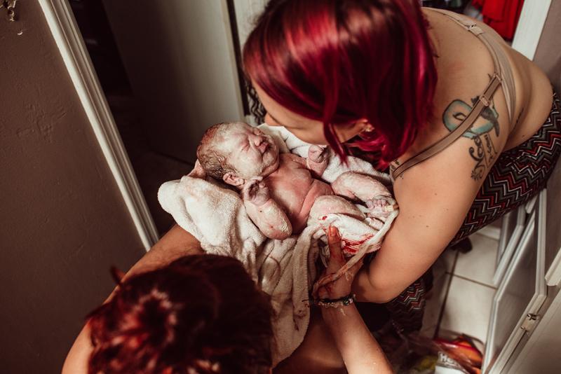 Salt Lake City Doula, newborn baby being passed between two women
