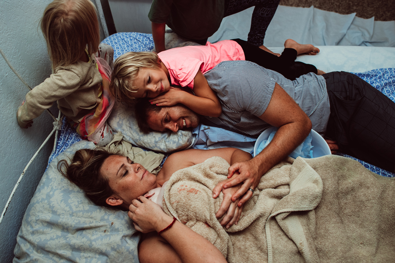 Birth Photography -woman lays on her bed with new baby, two daughters, and husband