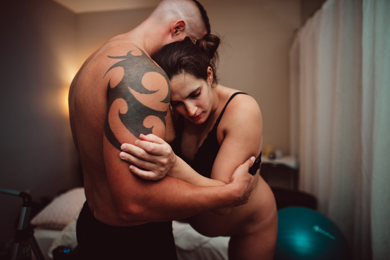 Birth Photography -many embraces his wife as she finds ways to get comfortable during labor pains